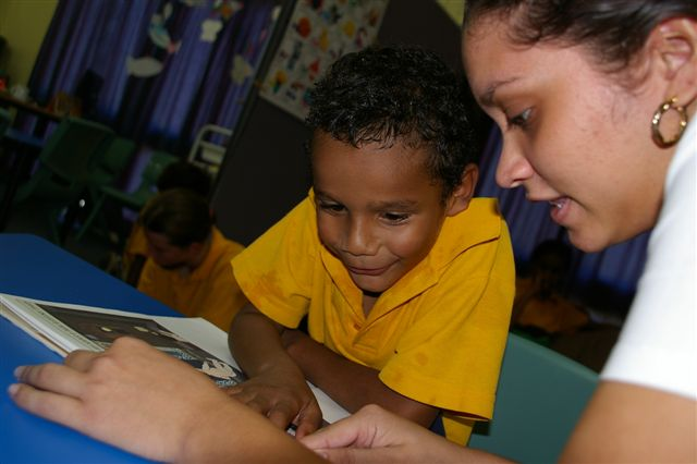 Photo of young aboriginal boy being educated by an aboriginal teacher